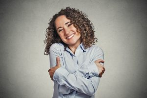 smiling woman holding hugging herself
